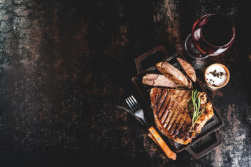 Grilled beef steak with spices on grill pan board, with and red wine glass. Copy space top view