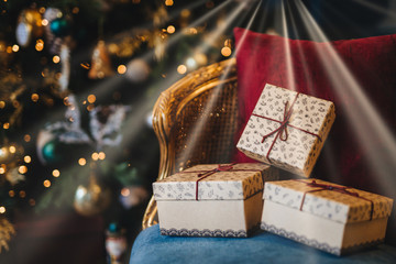 Picture of wrapped gift boxes lie on armchair against decorated New Year tree background. Preperation for holiday. Beautiful Christmas tree with garlands and presents indoors