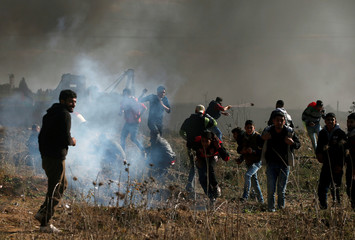 Palestinian protesters react to tear gas fired by Israeli troops during clashes near the border with Israel in the east of Gaza City