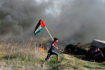 A protester holds a Palestinian flag as he runs during clashes with Israeli troops near the border with Israel in the east of Gaza City