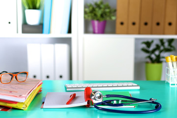 Doctor's workspace working table with patient's discharge blank paper form, medical prescription, stethoscope on desk