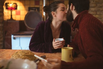 Couple kissing each other while having cup of coffee