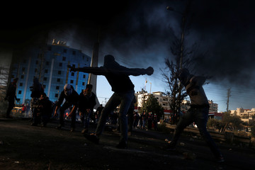 Palestinian protesters are seen during clashes with Israeli troops near the Jewish settlement of Beit El, near the West Bank city of Ramallah