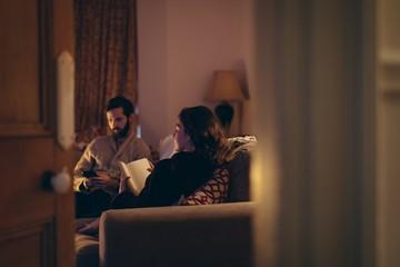 Man using mobile phone and woman reading novel in living room