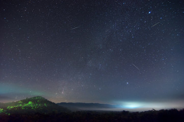 Milky way on hill with Leonid meteor shower.