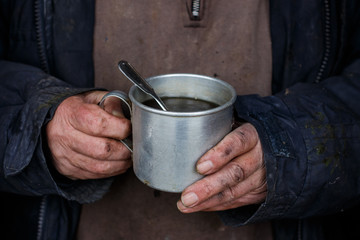 The poor man holding a Cup