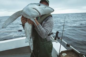 Fisherman holding shark fish