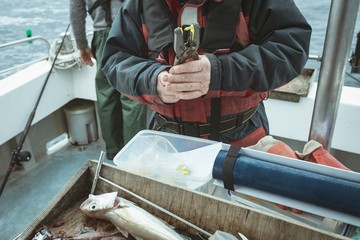 Fisherman pressing tag with hand tool