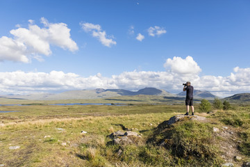 Great Britain, Scotland, Scottish Highlands, Glencoe, Rannoch Moor, Tourist photographing Loch Beinn Chaorach and Loch Ba