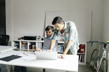 Two businessmen with laptop at desk in office discussing