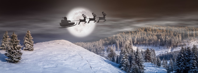 Christmas background, fairy tale scene with Santa on the sleigh  and reindeer flying on the sky ,in a winter wonderland landscape, scenery, with trees, snow and full moon in the Christmas eve