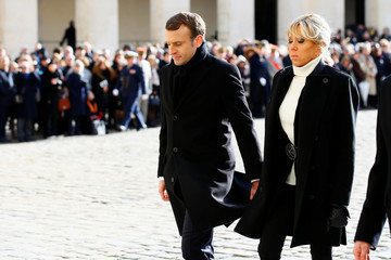 French President Emmanuel Macron and his wife Brigitte leave after a ceremony for Jean d'Ormesson at the Hotel des Invalides in Paris,