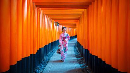 Asian women in traditional japanese kimonos at Fushimi Inari Shrine in Kyoto, Japan. Wall mural