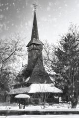 Snowing over a traditional Romanian wooden Church in black and white