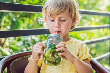 A little boy drinks water with mint and lime. Drink more water concept