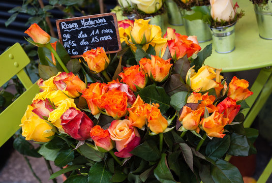 Florist shop. Yellow and orange roses bouquet with price tag on the green chair. Paris (France)