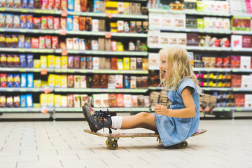 blonde child sitting on skateboard and having fun in supermarket with shelves behind