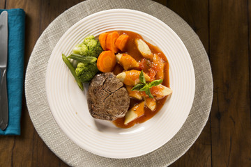 Delicious healthy food with grilled meat, gnocchi potato, red sauce and broccoli on the plate. View from the top.