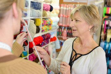 mature smiling blonde woman customer choosing spool in sewing store