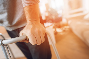 A man holds on to a walker for adults in a nursing home.