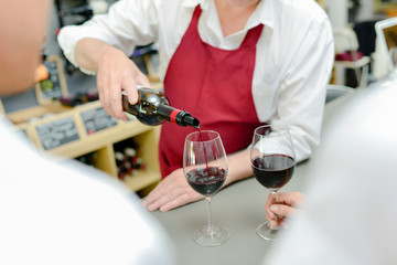 Worker pouring red wine into glasses