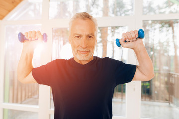 An elderly man is holding dumbbells in his hands in a nursing home.