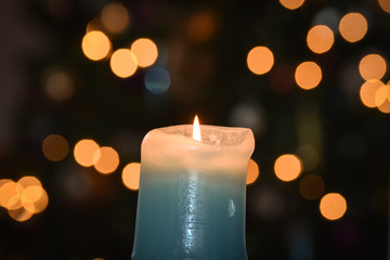 Burning candle with blurry christmas tree bokeh light background