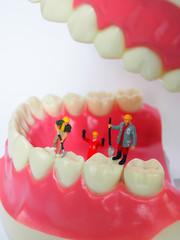 Miniature worker on plastic teeth of removable denture. Dental health concept.