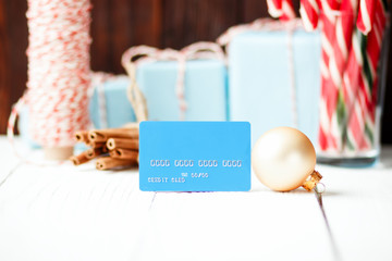 Christmas composition New Year selling discount concept blue credit card  with xmas gifts sweets toys balls rope cinnamon on white wooden table and brown background