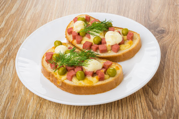 Hot sandwiches with sausage, cheese, green peas and mayonnaise