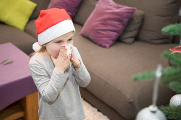 four years blonde cute girl with red Santa Claus hat, blowing her nose with white tissue next to Christmas tree at home