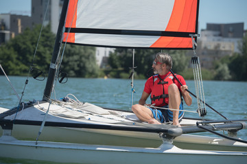 mature handsome man sailing on a lake