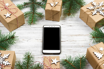 Christmas background with mobile phone with blank screen, gifts, fir branches on wooden background, copy space. Flat lay, top view. Christmas application, mock up