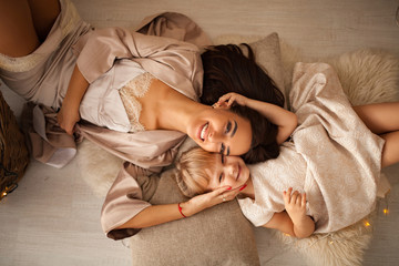 Mother with her daughter lies on floor and smiles. Top view.