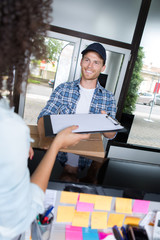 Delivery man passing clipboard for signature