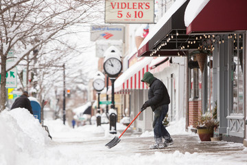 Man shovels snow during the first lake effect snowfall of the season in the Buffalo suburb of Orchard Park