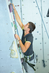young man climbing a wall at the gymnasium