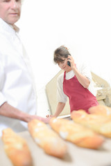 Baker holding baguettes, assistant on telephone