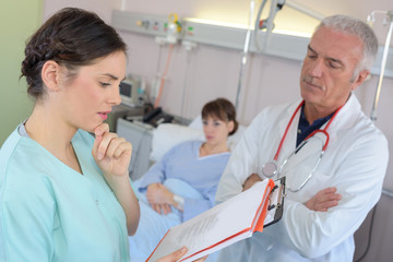 male doctor discussing some medical records with nurse