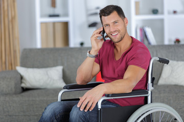 handsome man in wheelchair talking on his phone