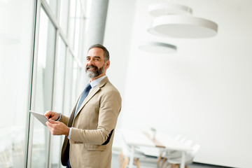 Middle aged  businessman with tablet in office