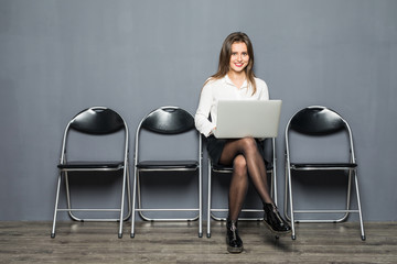 young smiling office worker woman sitting on wood floor chair using mobile laptop computer prepare interview meeting file in gray hall