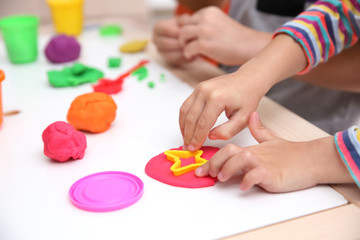 Little children engaged in playdough modeling at daycare, closeup