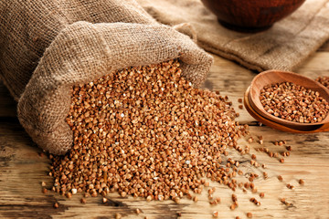 Bag with raw buckwheat on table