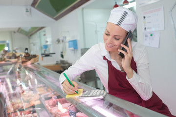 female butcher writing the order