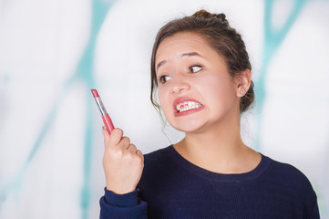 Close up of surprise beautiful woman doing miss lip with pink lipstick in a blurred background