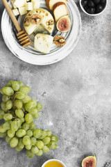 Various types of cheese on a gray background. Top view, copy space. Food background