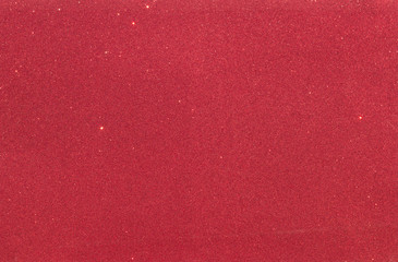 Red background with rough texture and bright spots. Christmas canvas.