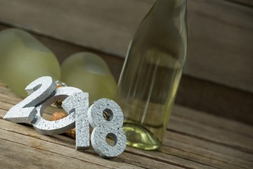 New year number 2018 and champagne bottles arranged on wooden