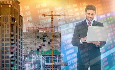 Double exposure of success businessman using laptop with Construction site with crane and building.with stock market, investment concept.Business concept.